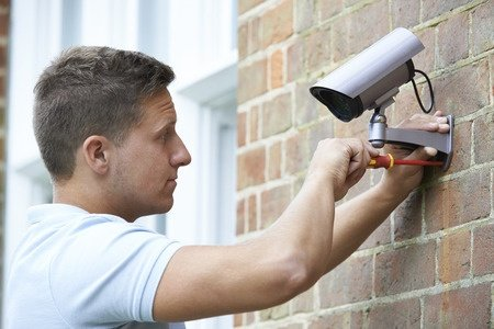 46129053 - security consultant fitting security camera to house wall